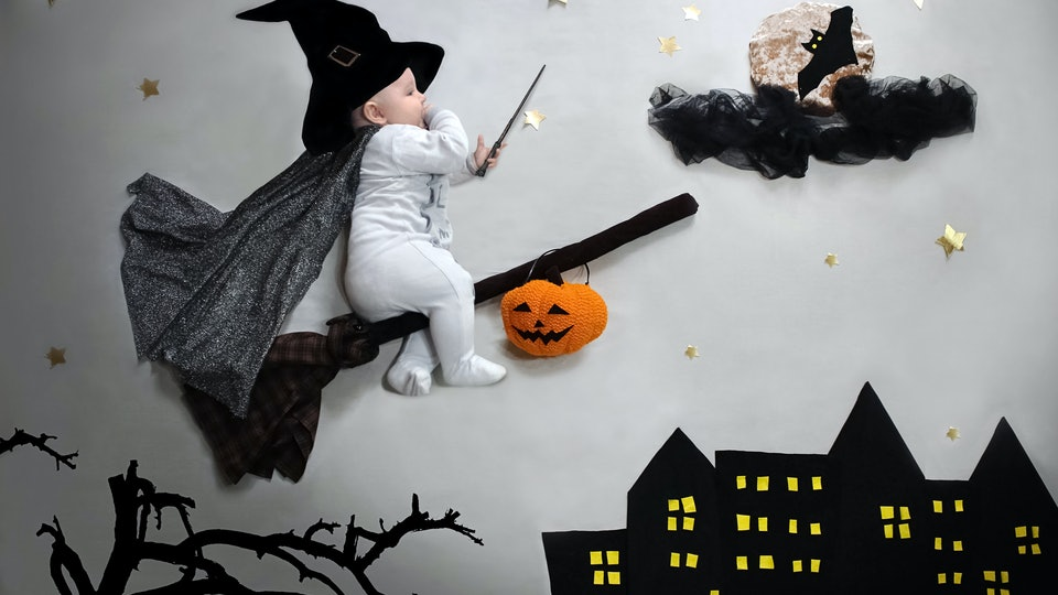 A last-minute Halloween costume for your baby can be as simple as this baby's white sleeper and black witch's hat.