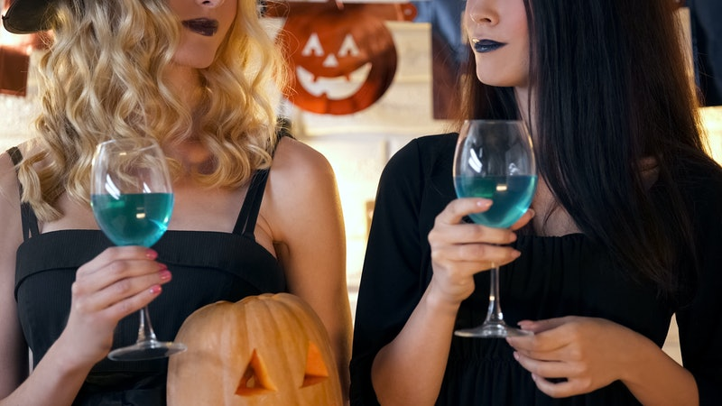 Witches holding cocktails and having fun at Halloween party, creepy celebration