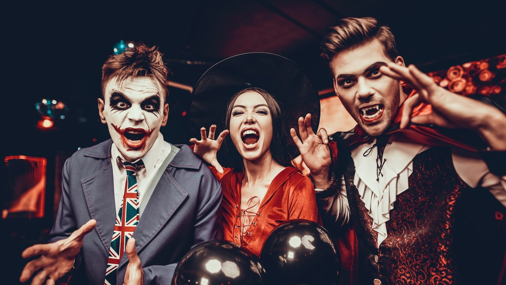 Three friends dressed in Halloween costumes as the Joker, a witch, and Dracula at a party.