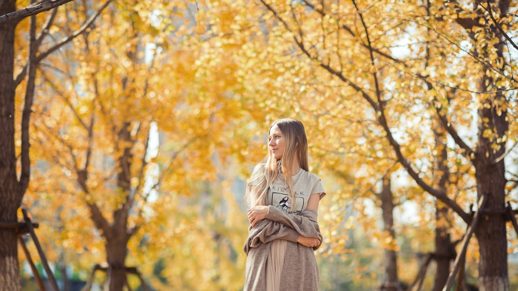 A woman with long blonde hair in a long dress and sweater walks through the yellow foliage in the fall.