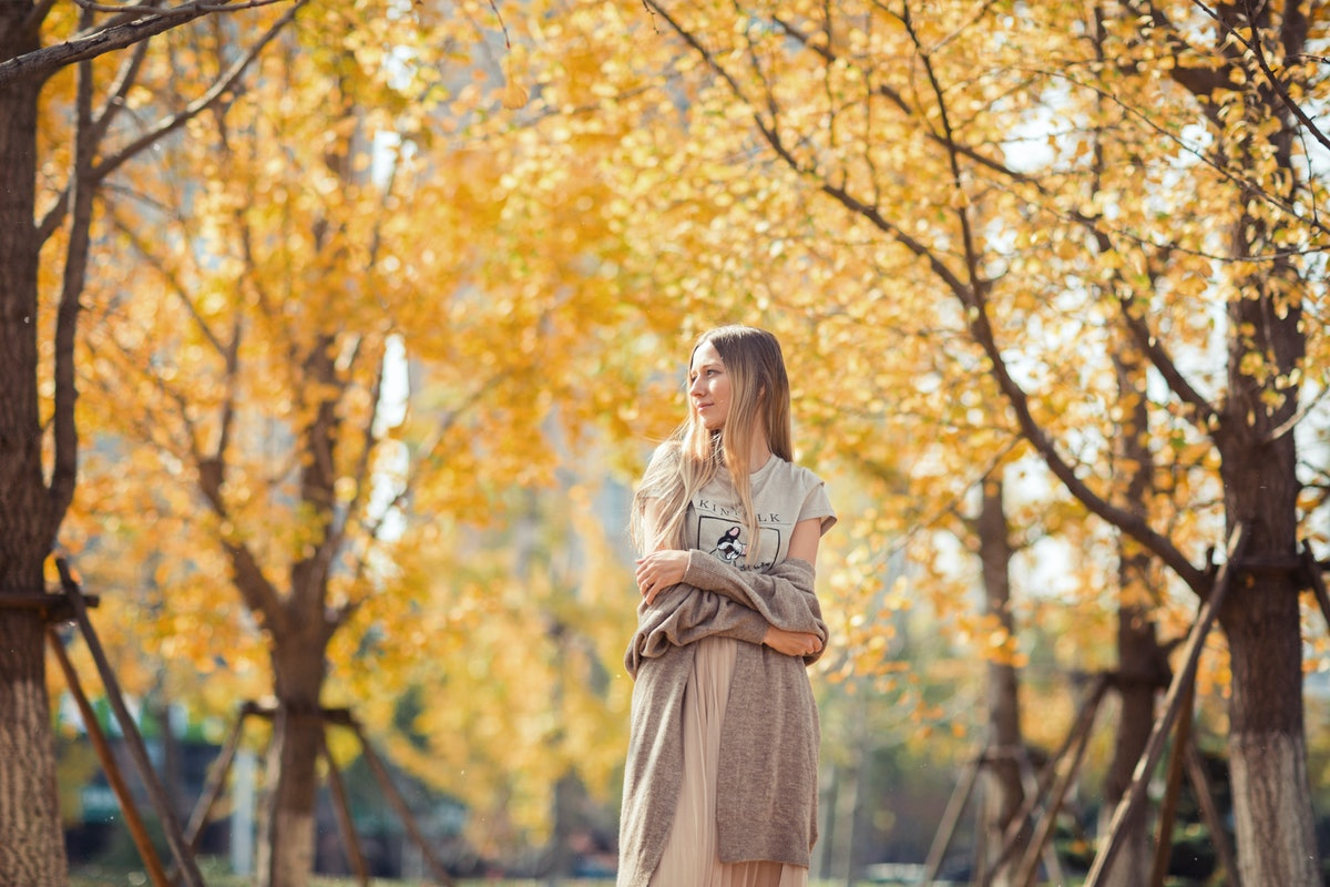 A woman with long blonde hair in a long dress and sweater walks through the yellow foliage in the fa...