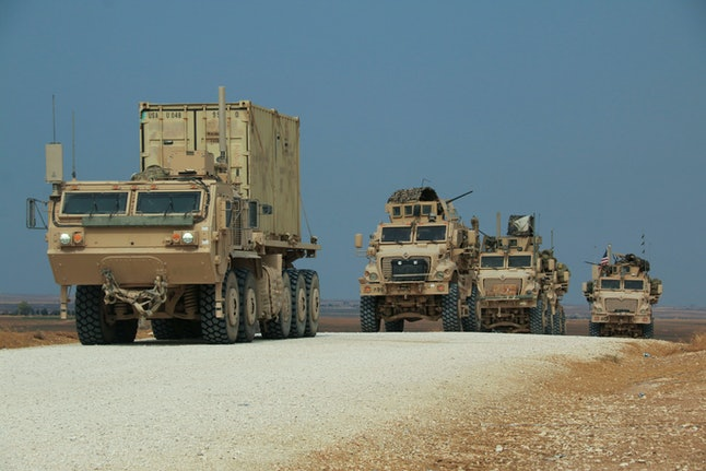 American military convoy stops near the town of Tel Tamr, north Syria, . Kurdish-led fighters and Turkish-backed forces clashed sporadically Sunday in northeastern Syria amid efforts to work out a Kurdish evacuation from a besieged border town, the first pull-back under the terms of a U.S.-brokered cease-fire