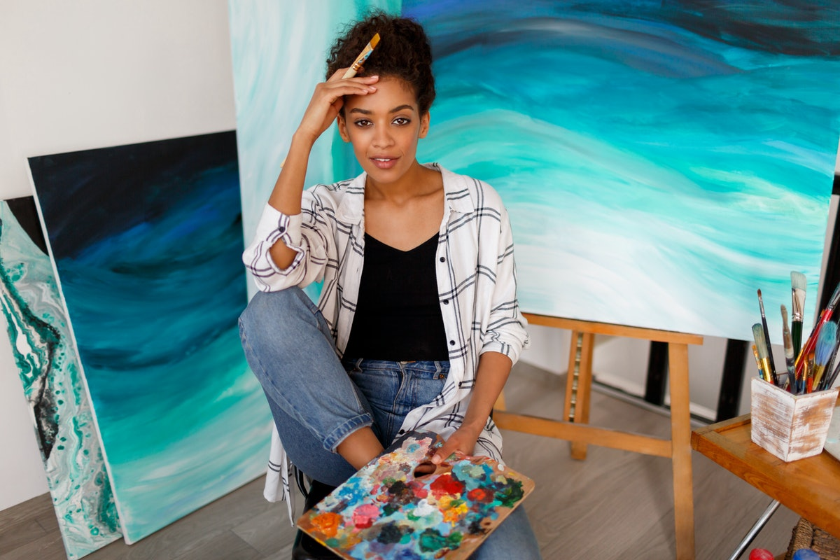 Close up portrait  of charming woman with dark skin posing in her art studio with abstract paintings.