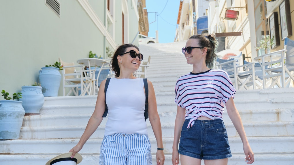 A mom and daughter walk down white steps together and smile.