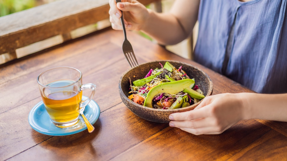 Woman eating quinoa salad at a wooden table outside. Here's what happens to your body when you stop eating meat.