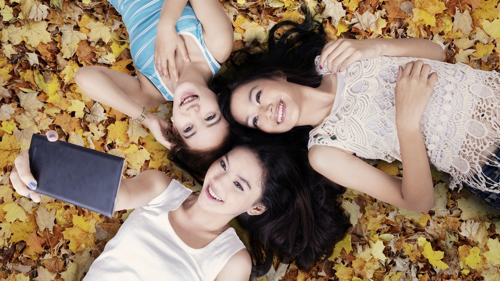 Unique perspective of three teenage girls taking picture with smartphone while lying down on autumn leaves