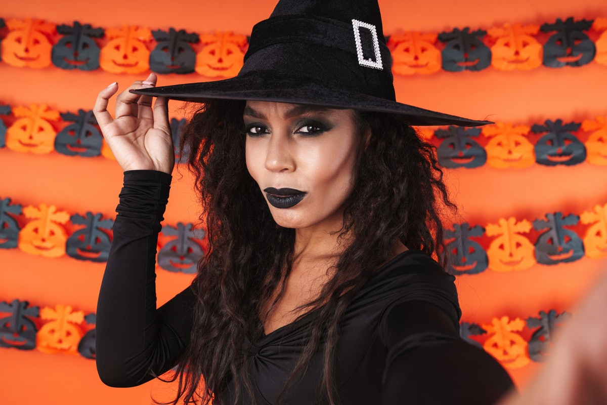 A girl in a witch costume takes a selfie in front of an orange wall with pumpkin cut-outs on Halloween.