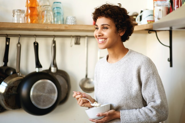 Portrait of smiling african american woman standing in kitchen eating breakfast cereal