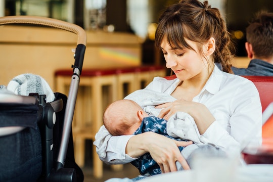 A young mother is breastfeeding her baby in a cafe while she is having a tea time