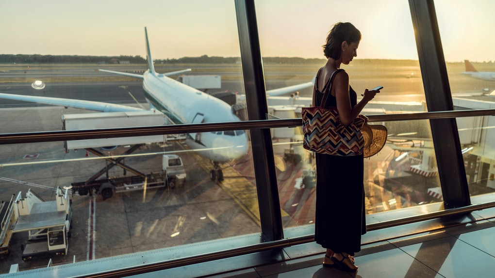 A woman with short hair and a long dress stands by the window in an airport and checks her phone while waiting to board her flight.