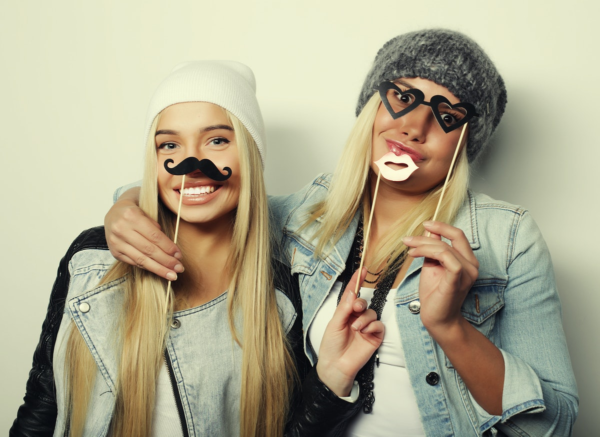 Two blonde friends pose in their simple Halloween costumes in front of a white background.