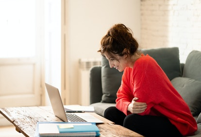 Close up of a cheerful casual beautiful woman wearing a bright red pullover working and studying on a laptop sitting on the couch at home. In working from home and surfing on the Internet concept.