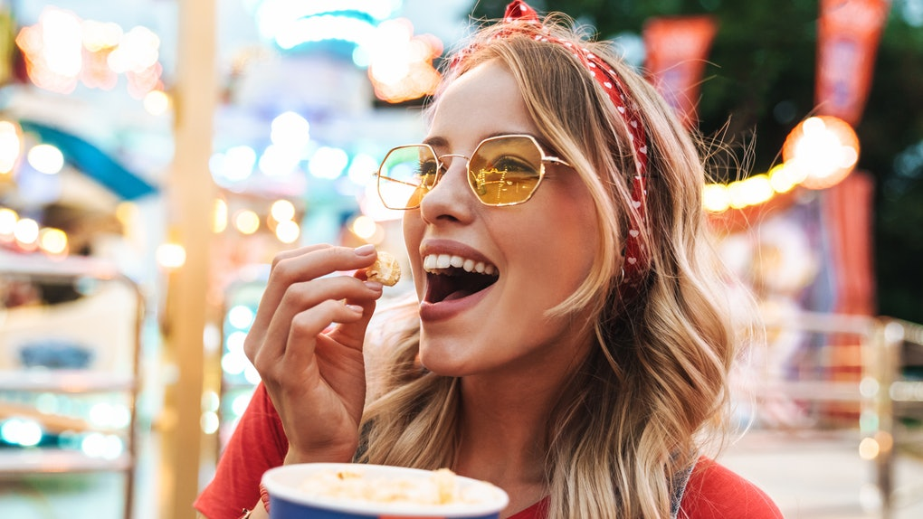 A happy blonde woman wearing sunglasses and a red T-shirt smiles while eating kettle corn in an amusement park.