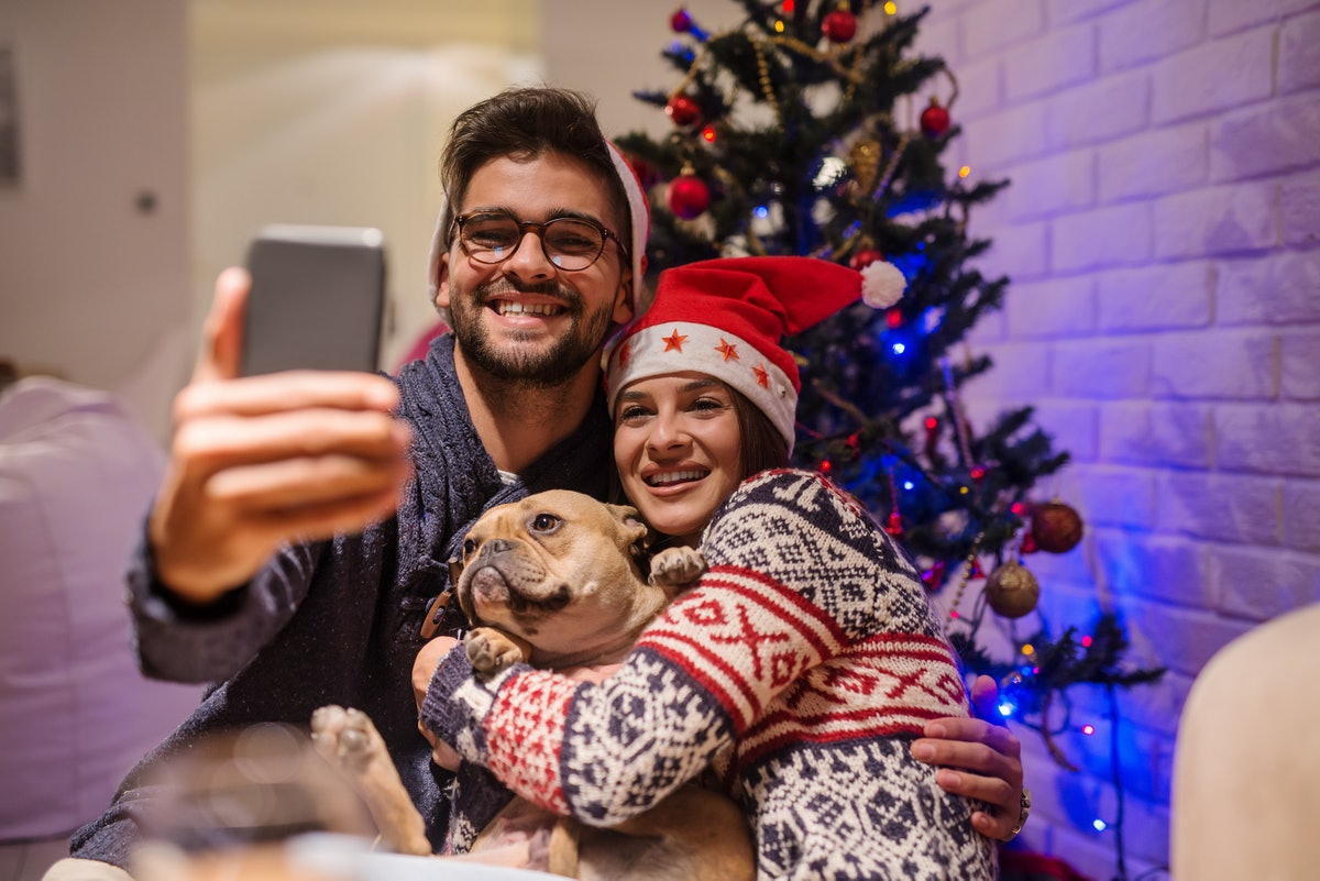 A smiling couple takes a selfie with their dog while wearing Christmas sweaters.