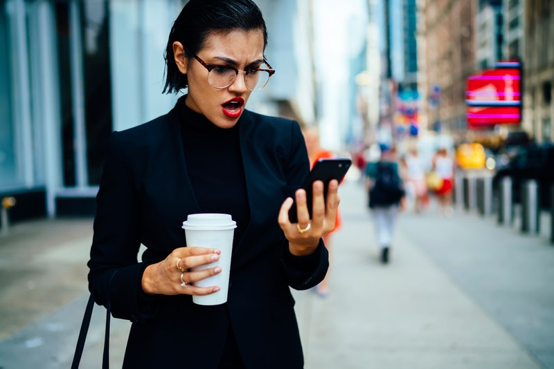 Angry woman in optical eyeglasses for vision correction with unhappy expression on face received email with bad news about selling shares of own company during coffee time on Manhattan street