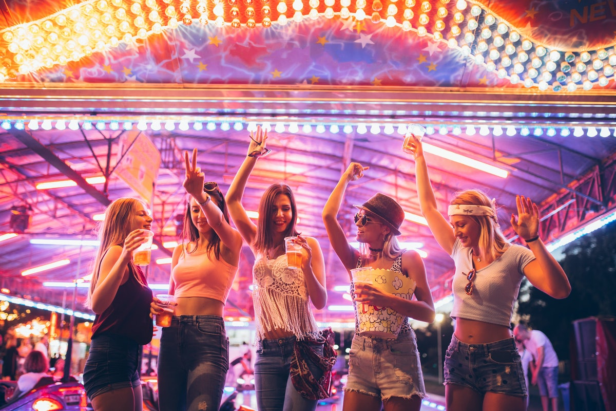 Five friends dance in an amusement park with kettle corn and drinks.