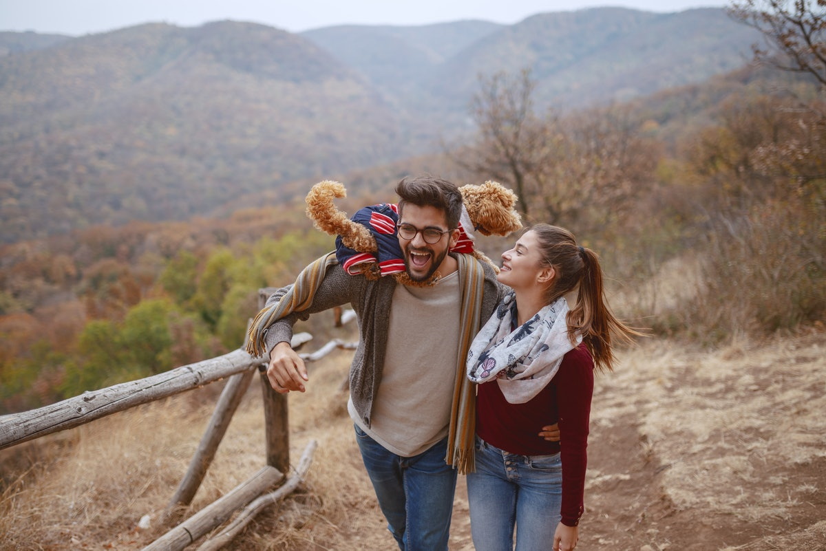 A cute couple dressed in casual clothes laughs and takes a walk in nature with their dog.