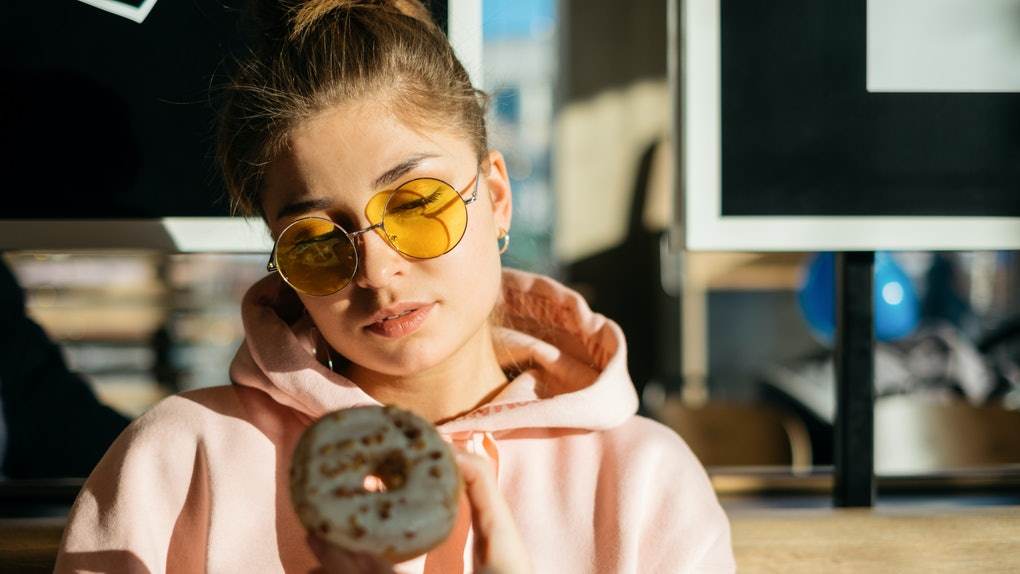A girl in a pink sweatshirt and yellow sunglasses looks at a pumpkin doughnut in her hand while sitting in the sun.