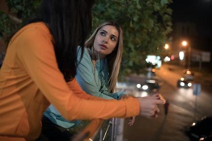 Women friends talking standing on the terrace, night city background