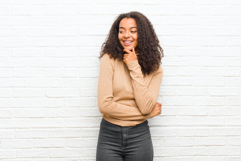 young black woman smiling with a happy, confident expression with hand on chin, wondering and looking to the side against brick wall