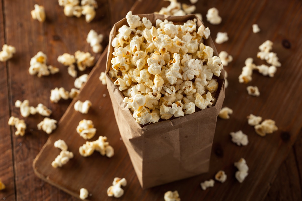 A top view of homemade kettle corn in a bag on a wooden table.