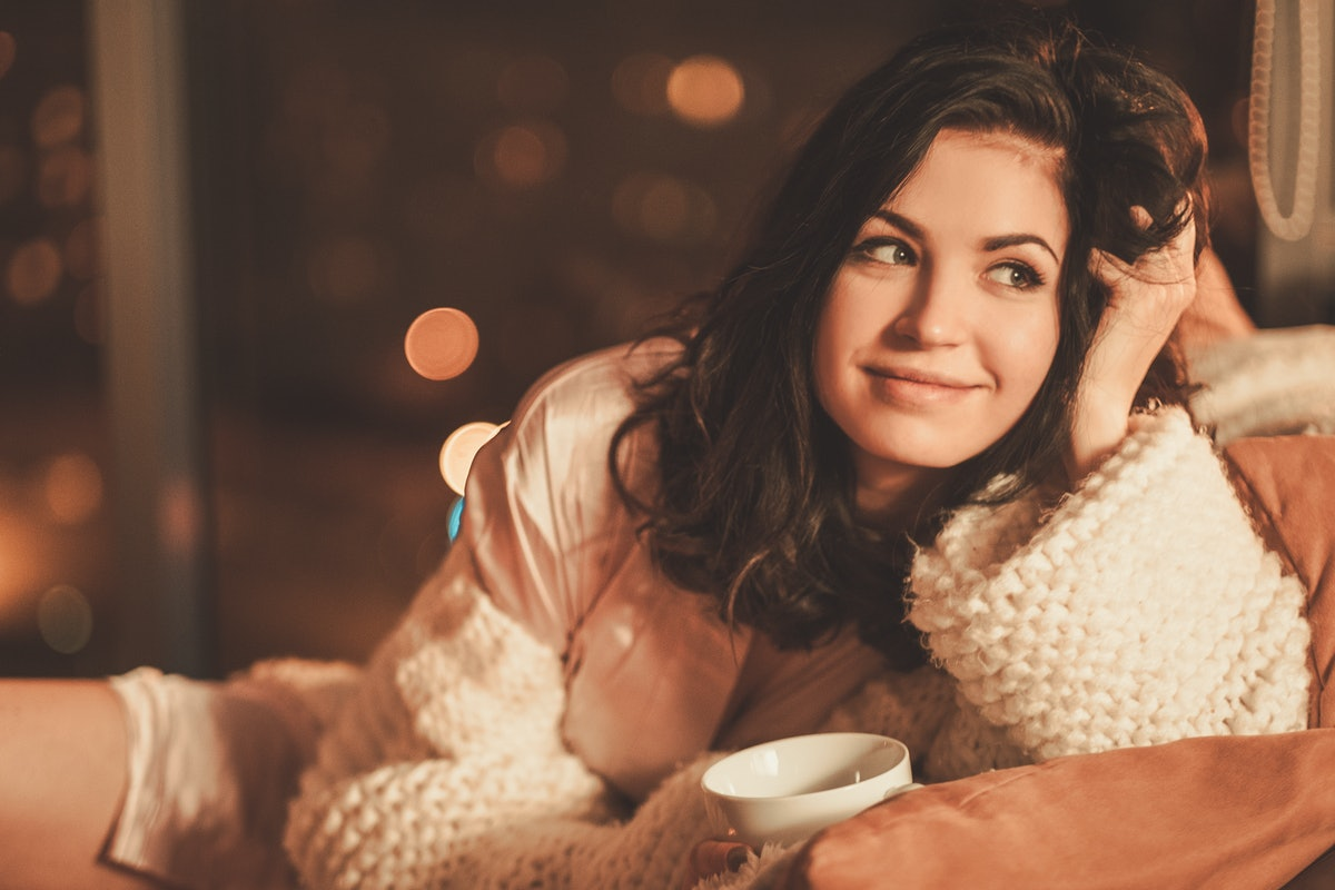Portrait of beautiful young woman with cup of hot drink in cozy home interior.