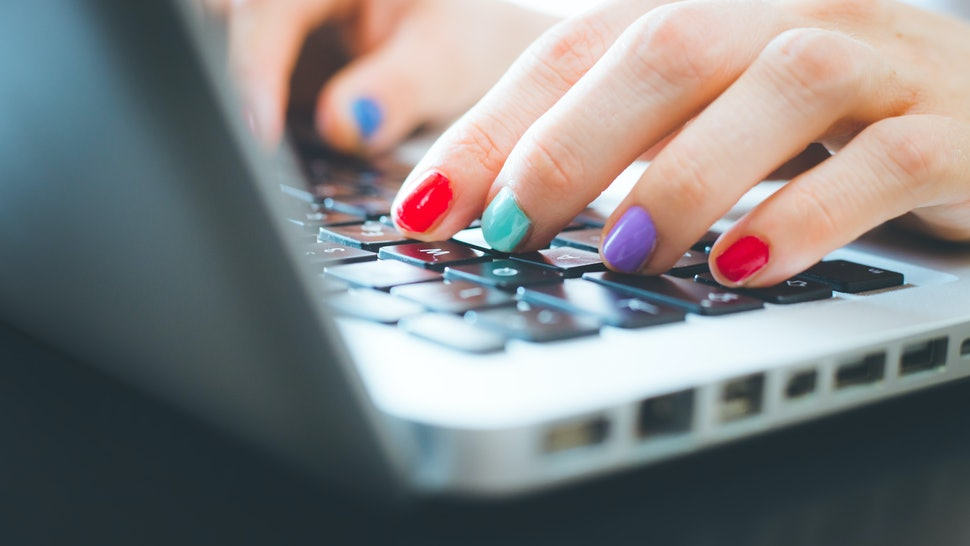 Woman fingers with colorful polished nails are typing on a laptop keyboard. Feminized leadership styles are proven to be more effective, but sexism keeps them from being implemented.