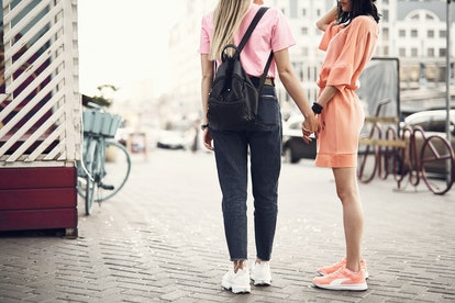 Two women going along city while holding hands together, on their way to a sober date