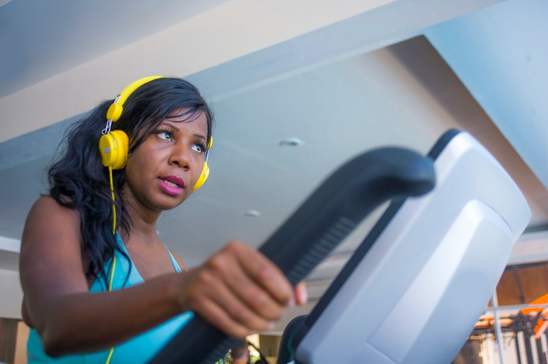 indoors gym portrait of young attractive and concentrated black afro American woman with headphones training elliptical machine workout at fitness club working hard in healthy lifestyle