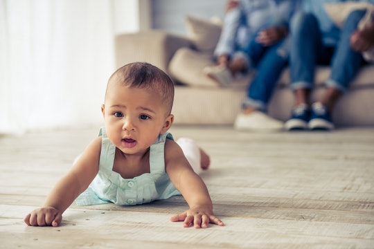 Adorable Afro American baby girl is looking forward with interest while crawling on wooden floor at home