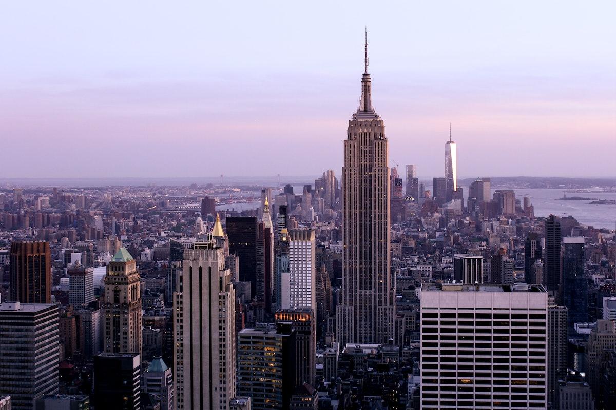 The sky is purple over the New York City skyline.