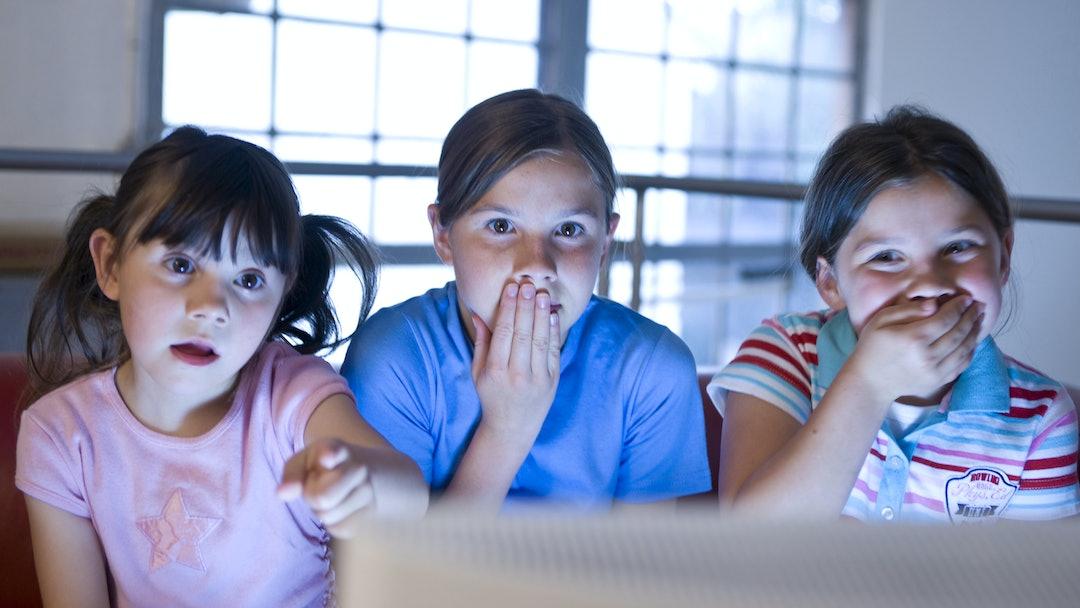MODEL RELEASED Three little girls secretly watching a video