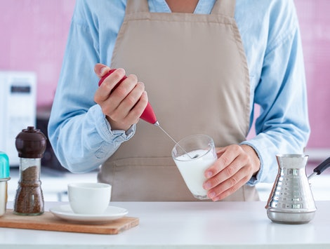 Woman in apron making aromatic coffee with using a milk frother at home