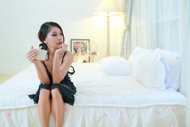 Bedroom concept of relaxation, A beautiful woman on bed with a cup of coffee