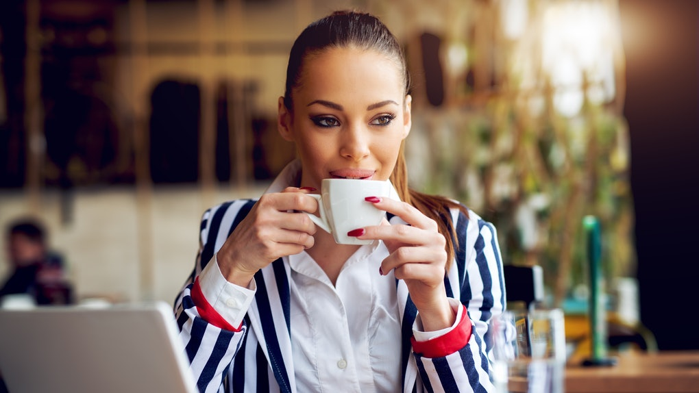 Young beautiful woman drinking coffee at cafe bar.