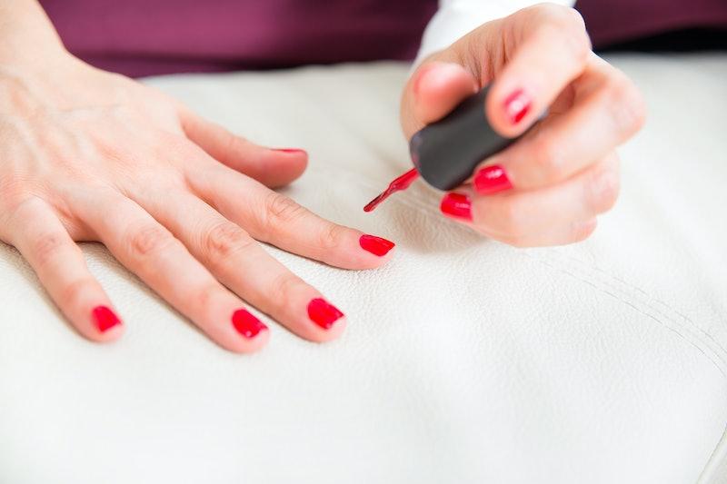 Pretty woman in bed applying nail polish