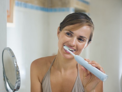 Young woman brushing teeth with electric toothbrush