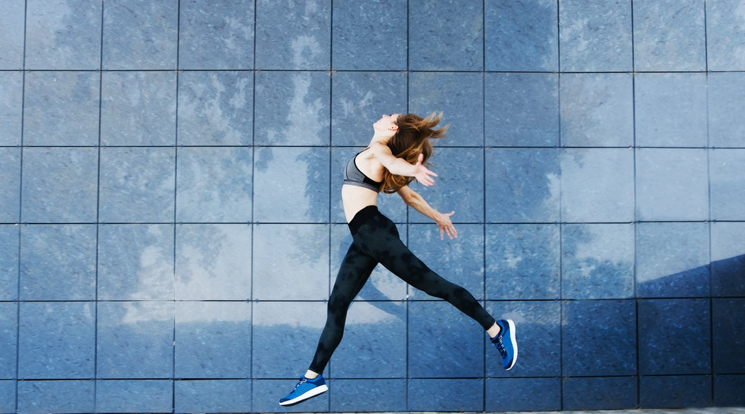 Young fitness woman dancing and jumping outdoors. Urban sport concept.