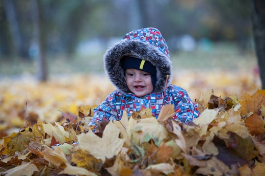 Funny baby in winter clothes (overalls) is sitting in a pile of leaves