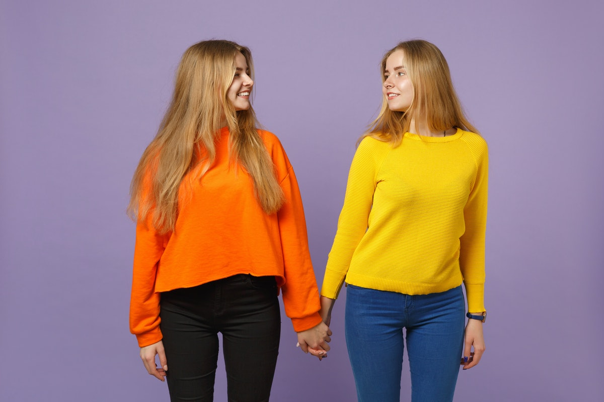 Two pretty young blonde twins sisters girls in colorful clothes holding hands looking at each other isolated on pastel violet blue wall background. People family lifestyle concept. Mock up copy space