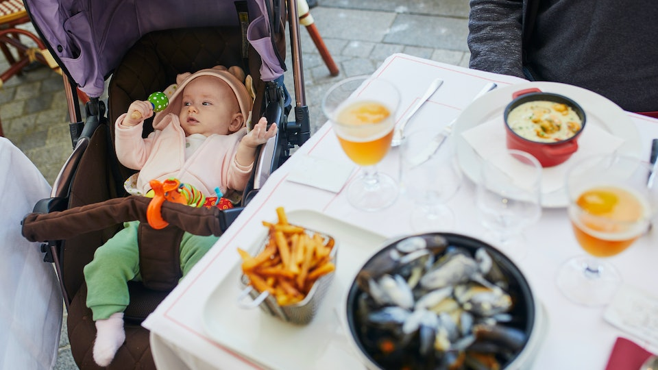 Cheerful baby girl in stroller near table in restaurant. Going out with kids. Boiled mussels in white sauce with French fries and apple cider, traditional dish in Normany (France) or Belgium
