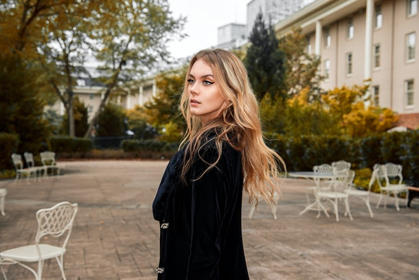 Fashion model. Gorgeous blonde young woman wearing a winter coat, jacket, nice hairstyle walking on the city park street in autumn fall winter time outdoors looking in distance. beautiful hair makeup