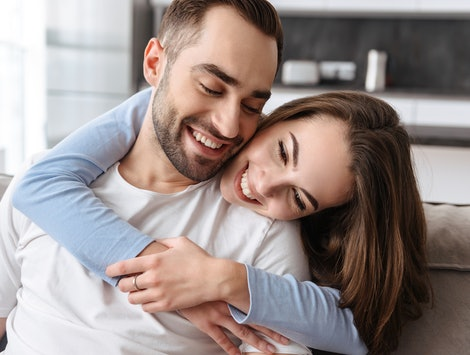 Image of couple in love man and woman in casual wear hugging together at home while sitting on sofa in living room