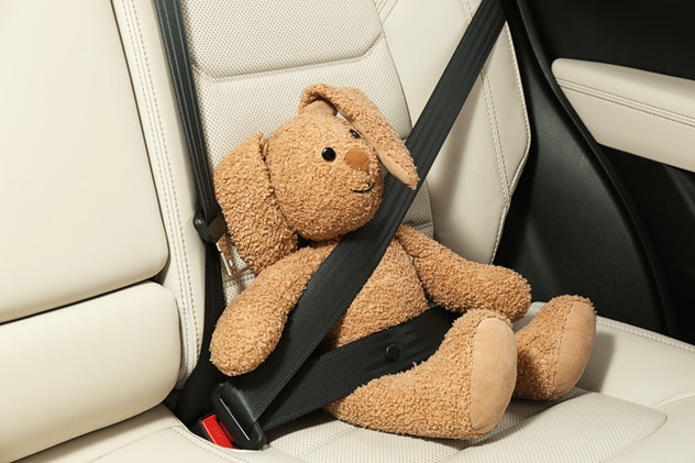 Cute stuffed toy rabbit buckled in backseat of car