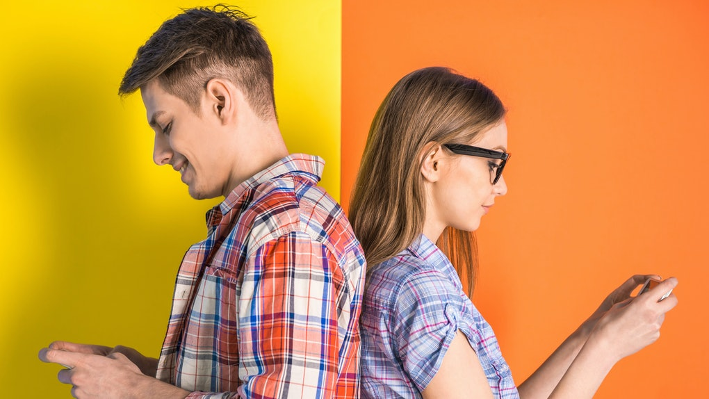 Portrait of young couple standing back to each other and looking at the phone.