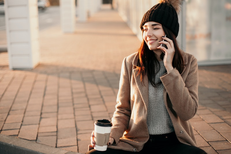 Happy smiling woman using phone and drink coffee sitting on the street.
