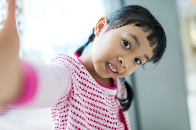 Asian little girl taking selfie.