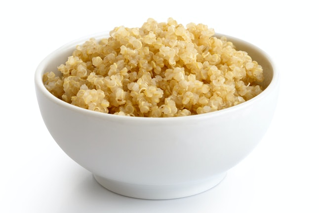 Cooked quinoa in white ceramic bowl isolated on white.