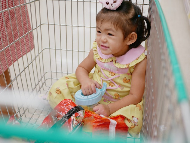 Little Asian baby girl sits in a cart, enjoys doing shopping with her mother.