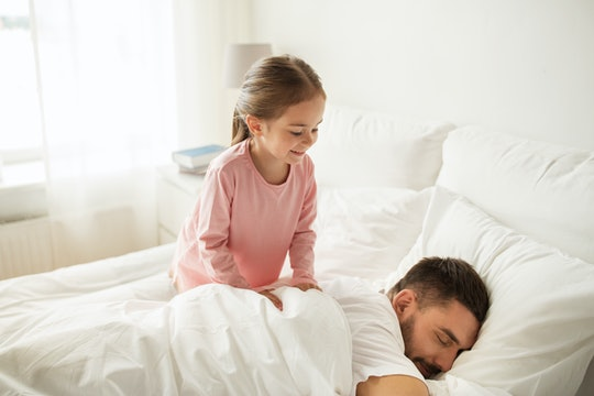 people, family and morning concept - happy little girl waking her sleeping father up in bed at home